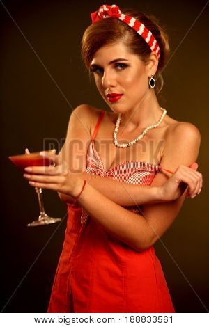 Pin up girl drink bloody Mary cocktail . Pin-up retro female style. Girl wearing red dress seduces men.