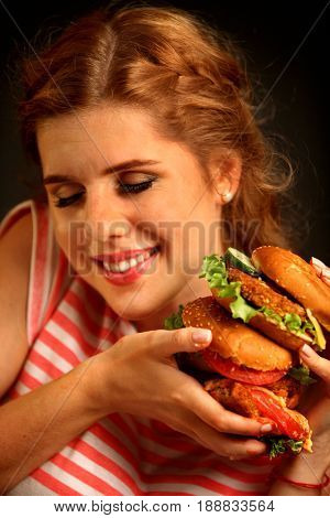 Woman eating burger and winks. Portrait of happy student going to seductively eat great sandwich for lunch. Joyful woman offers fast food on black background.