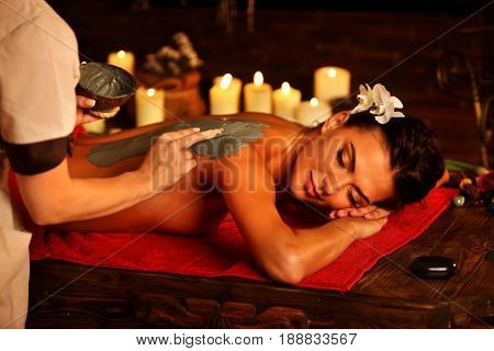Mud mask of woman in spa salon. Back massage with clay full body . Girl on luxary interior with candles in oriental therapy room. Female lying on red towel in wooden spa bed.