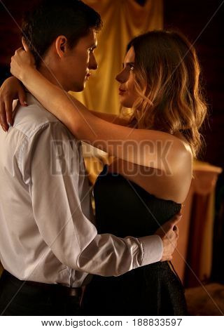Couple dancing and kissing indoor. Romantic evening interior for loving couple. Happy people in love. Girl looks passionately at her boyfriend. People celebrate graduation party.