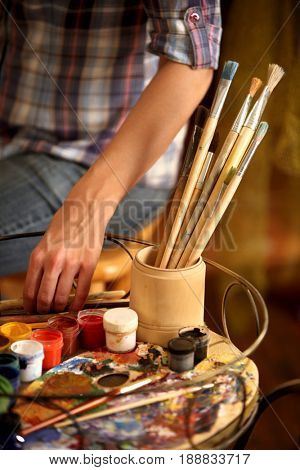 Artist painting on easel in studio. Cropped shot of hands paints of woman with brush. Indoor home interior for handmade crafts. Choosing a tool for creativity.