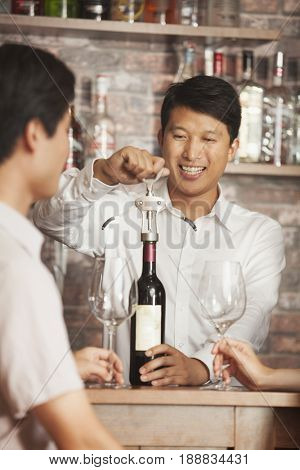 Chinese bartender uncorking bottle of wine