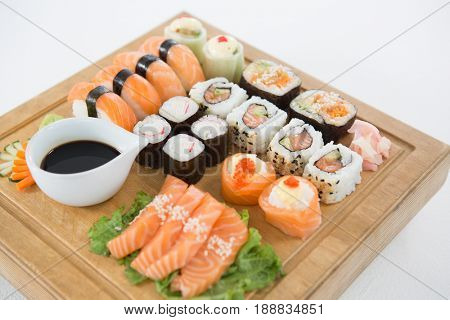 Set of assorted sushi served on wooden tray against white background