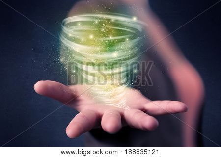 Bright green tornado in the hands of a young casual businesswoman