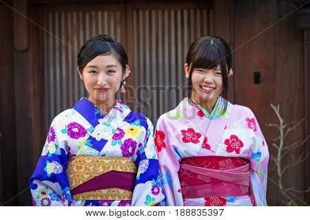 KYOTO, JAPAN - NOVEMBER 11, 2016: Young women wearing traditional japanese kimono walk on the street of Gion, Kyoto old town, Japan. Kimono is a Japanese traditional garment.