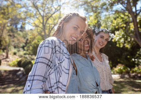 Portrait of happy female friends standing together with arm around in park on a sunny day