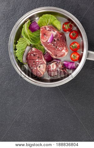 Sirloin chops and ingredients in frying pan against black background