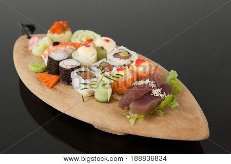 Assorted sushi set served in wooden boat plate against black background