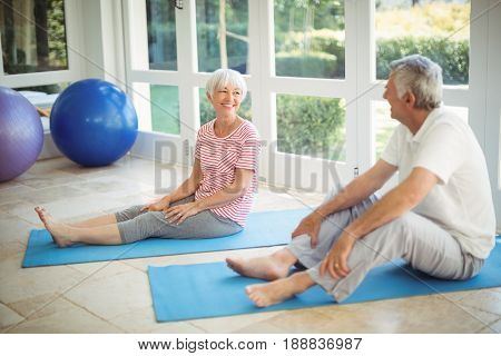 Happy senior couple interacting while performing exercise on exercise mat at home