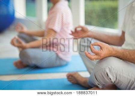 Mid-section of senior couple performing yoga on exercise mat at home