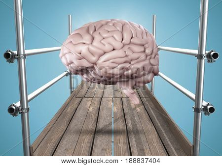Digital composite of Brain with flare on scaffolding against blue background