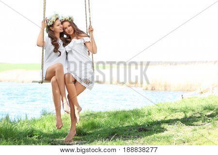 Two beautiful young women on swing near river