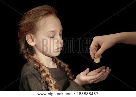 Woman giving money to poor little girl on black background