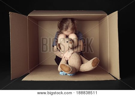 Poor little girl with toy bear sitting in cardboard box on black background