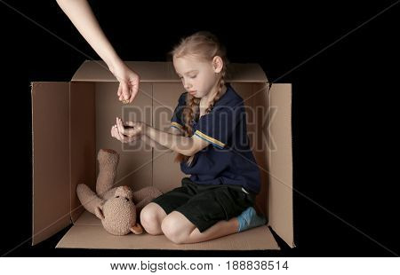 Woman giving money to poor little girl sitting in cardboard box on black background