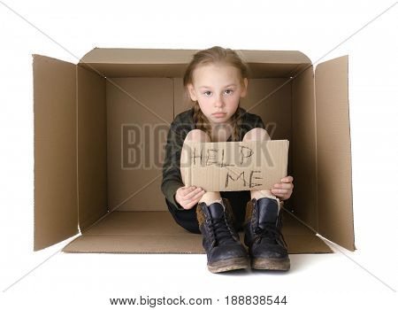 Poor little girl with piece of cardboard sitting in cardboard box on white background