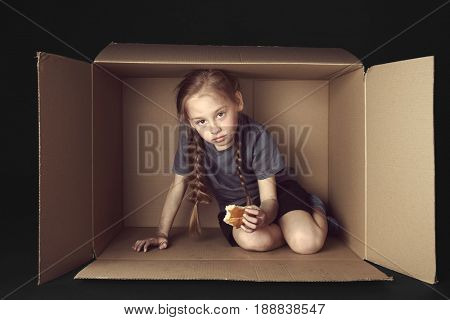 Poor little girl with piece of bread sitting in cardboard box on black background