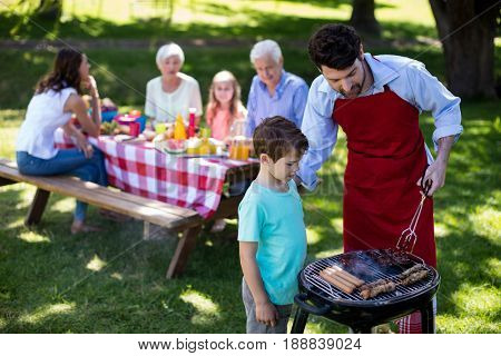 Father and son barbequing in the park during day
