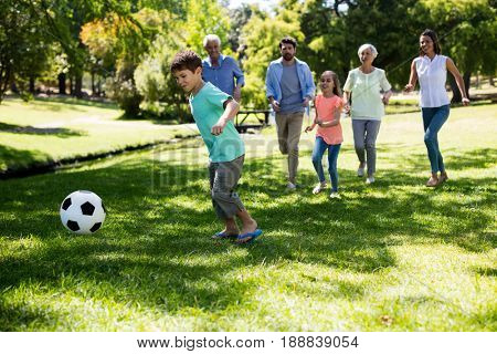 Cheerful multi generation family playing football in park