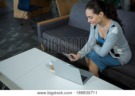 Female business executive sitting on sofa using mobile phone