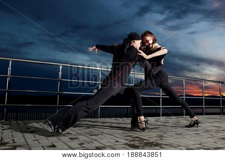 Senior couple ballroom dancing on dark sunset  background