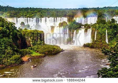 Iguazu Falls National Park on the border of Argentina, Brazil and Paraguay. Small boats transport curious tourists to waterfalls. The concept of extreme and exotic tourism