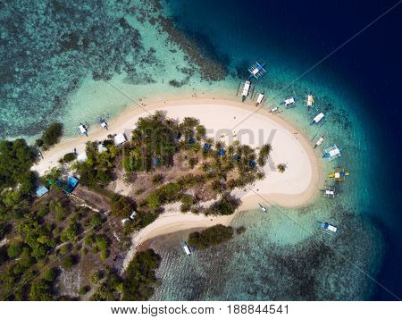 Aerial top view of tropical island beach with boats surrounded by turquoise sea. Palawan