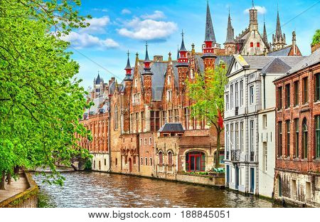 Medieval town Bruges in Belgium. Panorama and landscape vintage channel with old brick house broach on roof. Spring sunny day blue sky white cloud end green trees.