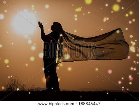 Woman with her hands up on sunset