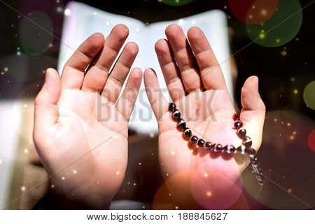 Muslim man hands holding rosary with quraan