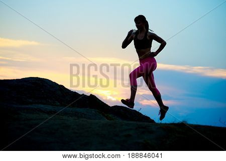 Young Woman Running to the Top of the Mountain at Sunset. Active Lifestyle Concept.