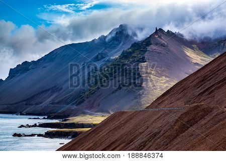 The main highway in Iceland on the slopes of volcanic mountains. Beach Atlantic Ocean. Summer tour in the Nordic countries. The concept of extreme northern tourism