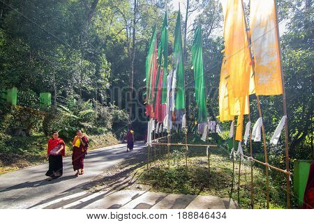 SAMDRUPTSE SIKKIM INDIA - OCTOBER 20TH 2016 : Monks walking the road to Samdruptse statue prayer flags waving on the side of road . Samdruptse is a huge buddhist memorial statue in Sikkim India.