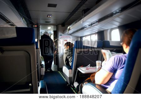 UNITED STATES - February 25, 2012: Conductor walks past passengers riding on an Amtrak train