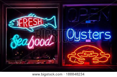 COOS BAY, OREGON, UNITED STATES - September 2, 2009: Restaurant window filled with a variety of seafood neon signs at night