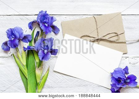 blank white greeting card with blue iris flowers bouquet and envelope on white wooden background. top view. mock up