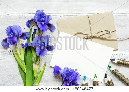 blank white greeting card with blue iris flowers bouquet and envelope with colorful pencils on white wooden background. top view. mock up