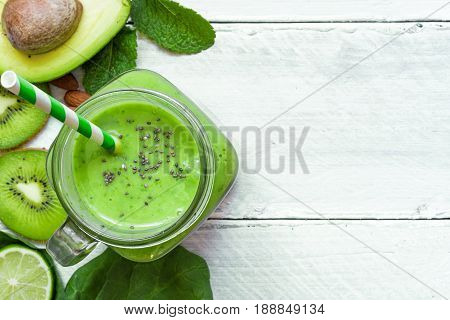 green healthy smoothie with avocado spinach kiwi lime and chia seeds in a glass jar with a straw over white wooden background. top view with copy space. shallow depth of field