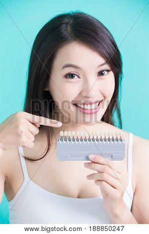 woman take tooth color palette with whiten concept
