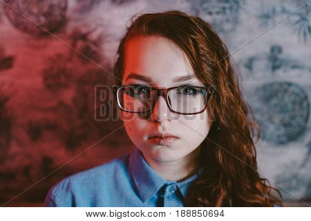 Artistic portrait of a beautiful red-haired girl wearing red glasses and a blue shirt. Piercing in the lip.