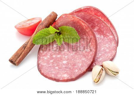 Three thinly sliced slices of smoked sausage salami with melissa leaves, hazelnut kernel, half a tomato and cinnamon stick