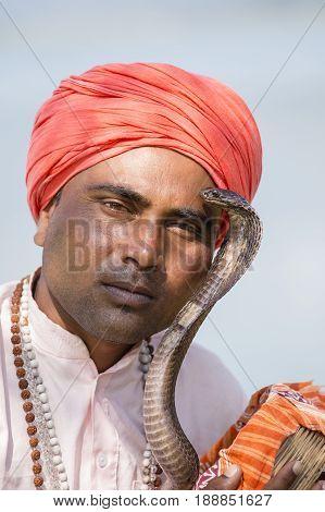 POKHARA NEPAL - OCTOBER 07 2016 : Portrait of snake charmer adult man in turban and cobra sitting near the lake
