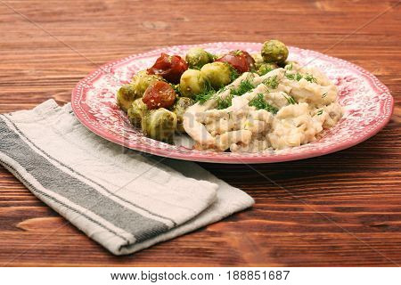 Tasty chicken meat under creamy sauce with brussels sprouts garnish. Low fat healthy eating concept.