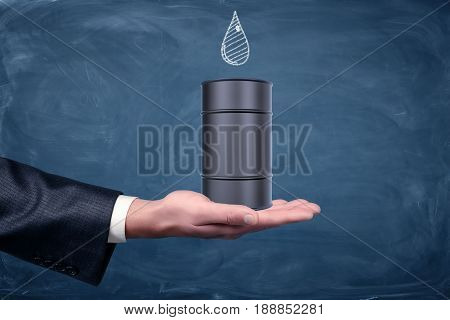 A businessman's hand turned up and a small black oil barrel standing on it with a drawn drop on chalkboard. Oil and gas business. Procurement industry. Commodities trading.