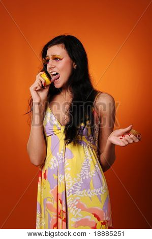 beauty young woman in yellow dress lick lemon, isolated on orange background