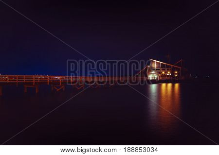 House on water at night. pier and a house by the sea