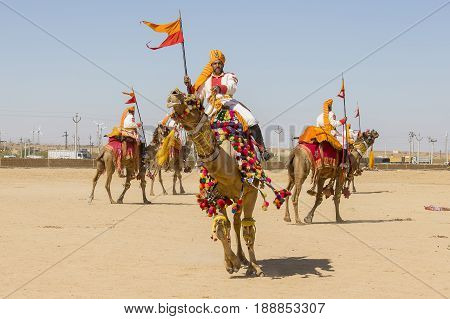 JAISALMER INDIA - FEBRUARY 09 2017 : Camels and indian men wearing traditional Rajasthani dress participate in Mr. Desert contest as part of Desert Festival in Jaisalmer Rajasthan India
