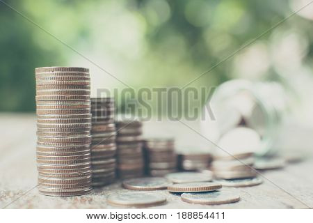 Money coin stack step growth with blurred background jar and green leaf Saving money and investment concept