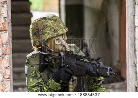 Portrait of armed woman with camouflage. Young female soldier observe with firearm. Child soldier with gun and gas mask in war hearth house ruins background. Military army people concept