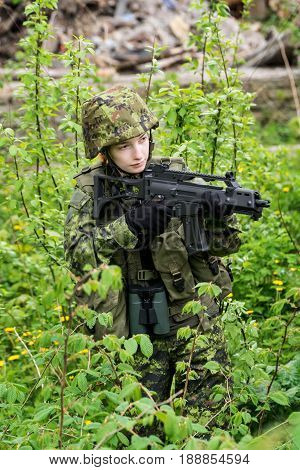 Portrait of armed woman with camouflage. Young female soldier observe with firearm. Child soldier with gun and in war hearth house ruins background. Military army people concept